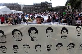Manifestante segura faixa com fotos de estudantes da escola normal de Ayotzinapa. Eles foram entregues por policiais a um grupo de narcotraficantes locais e estão desaparecidos.